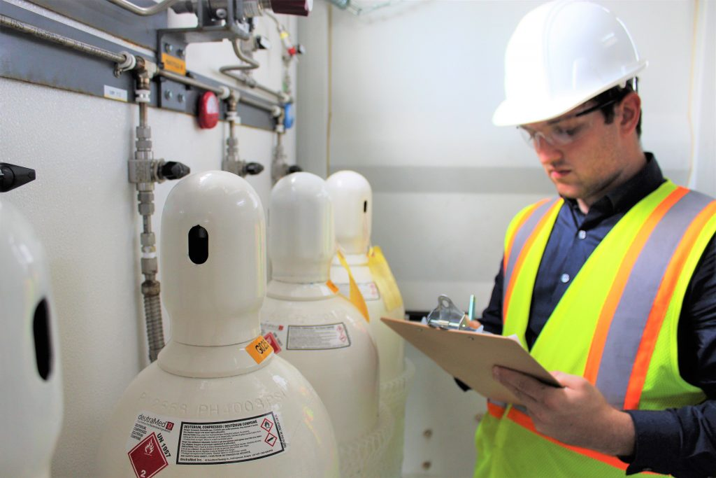 An engineer working on updating a list and reviewing the Deuterium Products tanks